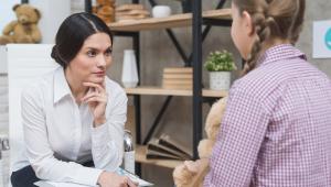 Com a mão no queixo, psicóloga atende uma menina de tranças, que está de costas e aparece parcialmente, segurando um bicho de pelúcia