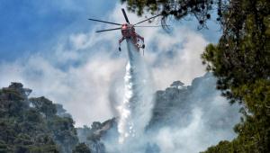 Helicóptero do Corpo de Bombeiros da Grécia lança jato de água para tentar apagar o incêndio florestal no Peloponeso