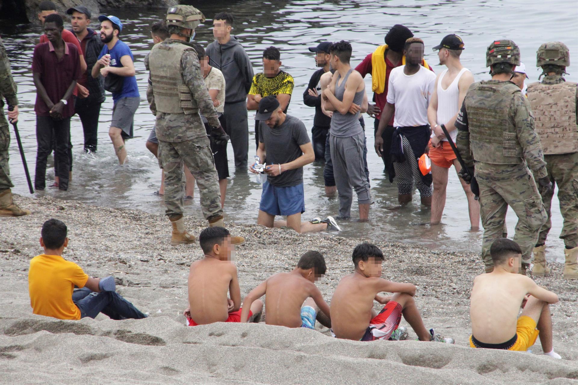 Soldados formam um cordão de isolamento em praia de Ceuta enquanto jovens marroquinos aguardam de pé ainda dentro d'água
