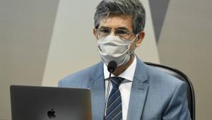 Homem de máscara e óculos prestando depoimento