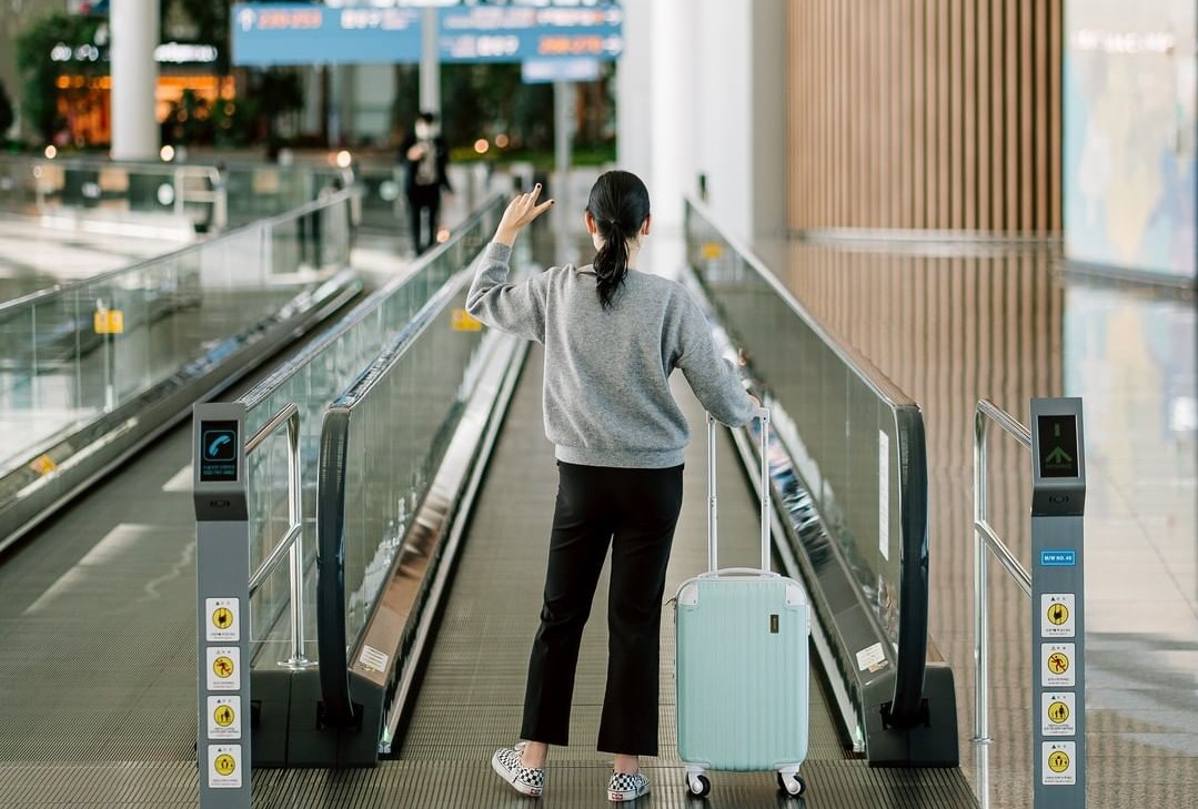 Sul-coreana com mala de rodinhas em frente a esteira do Aeroporto Internacional de Incheon