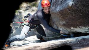 Homem subindo em uma montanha