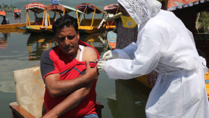 Homem da Caxemira indiana recebe uma injeção de vacina contra Covid-19 durante uma campanha de vacinação nas margens do Lago Dal em Srinagar