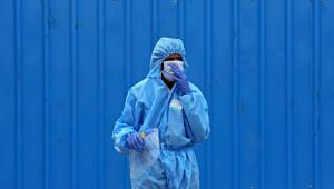Pessoa usa equipamento de proteção individual durante cremação de vítimas da Covid-19 na Índia