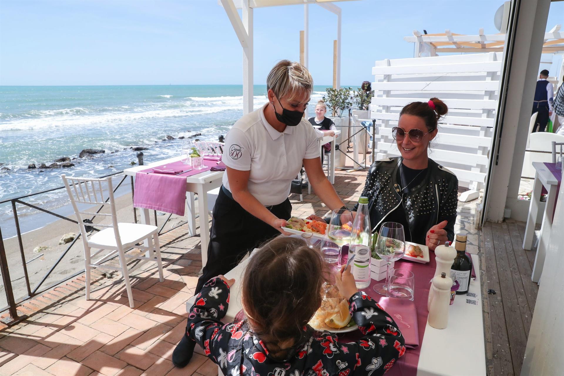 Um garçom com máscara facial atende clientes em um restaurante à beira-mar em Ostia, perto de Roma