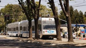 Um trem leve da VTA passa como policiais investigam cena de um tiroteio