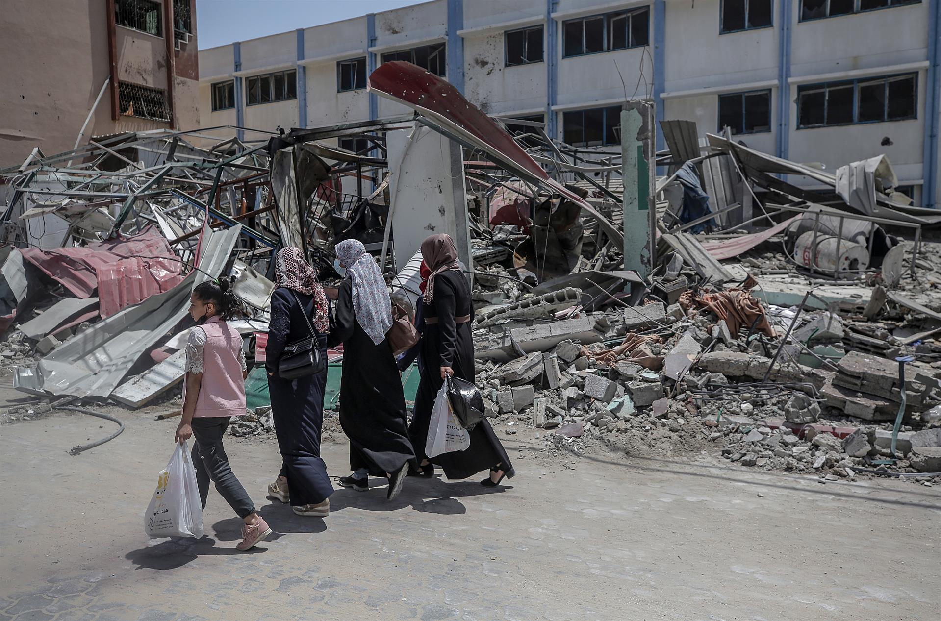 Pessoas passam pelos escombros de um prédio do Ministério do Interior do Hamas após o ataque aéreo de Israel contra a Faixa de Gaza
