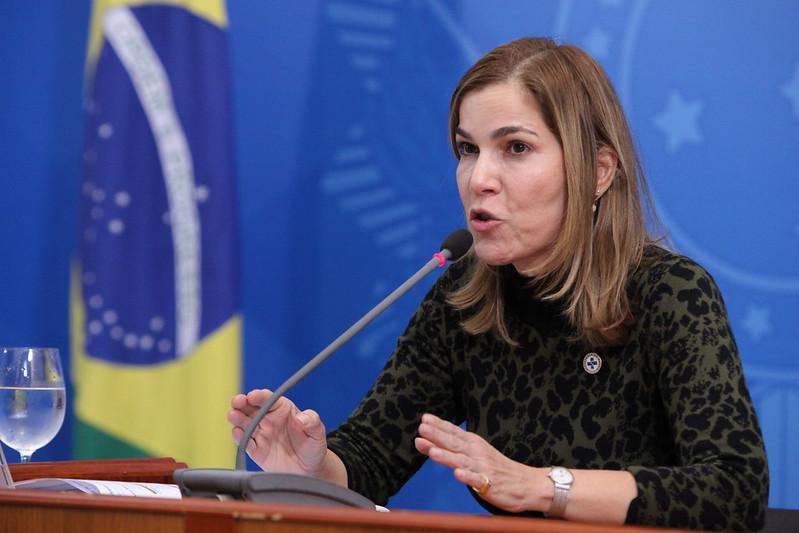 Foto de mulher falando ao microfone com as mãos levemente levantadas em uma mesa. Usa uma blusa de estampa de tigre, preta e verde-escura de manga longa