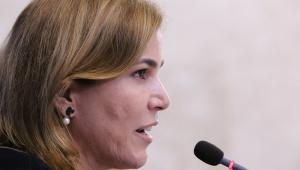 Foto de perfil de mulher falando no microfone. É branca de cabelos loiros e fala em um microfone pequeno.