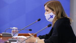 Foto de perfil de mulher falando no microfone. É branca de cabelos loiros e fala em um microfone pequeno. Ela usa uma máscara de proteção do SUS
