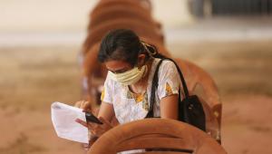 Mulher preenche formulário antes de receber a vacina contra a Covid-19 durante campanha em Bangalore, Índia