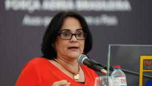 Ministra Damares Alves falando em microfone. Tem cabelos curtos pretos, usa óculos preto e vestido e acessórios vermelhos.