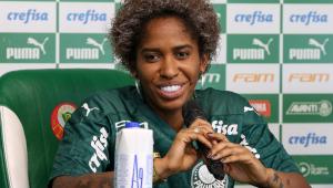 A atacante Chu, uma jogadora negra, beste a camisa do Palmeiras e, sentada, dá entrevista na sala de imprensa do clube