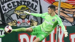 Com camisa e calção verde claro, o goleiro Vinicius, do Palmeiras, se arma a reposição de bola no estádio do Corinthians; atrás dele, na arquibancada, aparece uma faixa estendida da torcida alvinegra Camisa 12