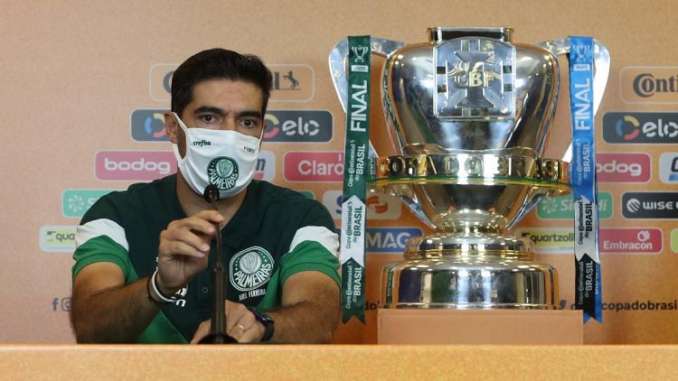 Sentado em uma bancada, de máscara e camisa verde esportiva do Palmeiras, o português Abel Ferreira concede entrevista coletiva com a taça da Copa do Brasil à sua esquerda
