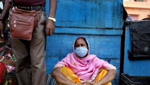 Usando máscara, mulher indiana senta-se no chão de estação de trem em Kolkata