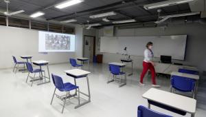 Sala de aulas em escola de São Paulo com retroprojetor, carteiras (separadas com distanciamento apropriado) e um monitor; mulher passa pela sala