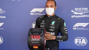 De máscara branca e macacão preto da Mercedes, Lewis Hamilton segura um troféu comemorativo em forma de pneu pelas 100 poles