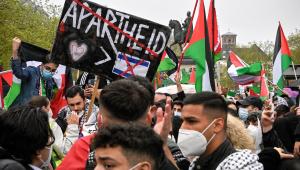 Em Colônia, na Alemanha, manifestantes seguram cartaz que insinua que Israel mantém a Palestina em um regime de apartheid