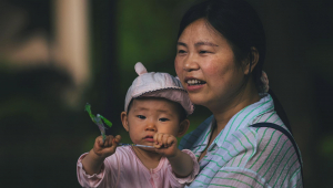 Mulher caminha com um bebê em uma rua de Xangai, China