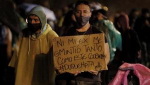 Homem segura cartaz amarelo com dizeres em espanhol