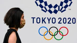 Mulher usando máscara de proteção facial passa diante de logo dos Jogos Olímpicos de Tóquio