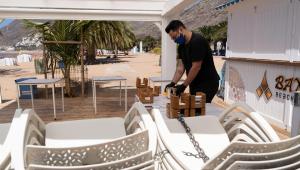 Funcionário arruma cadeiras de praia nas Ilhas Baleares, Espanha