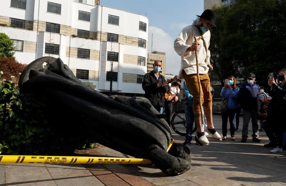 Enquanto um homem com chapéu, camisa e calça pula em frente à estátua de Gonzalo Jiménez de Quesada, outras pessoas tiram foto do monumento caído no chão