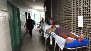 Paciente aguarda em maca deixada no corredor de um hospital