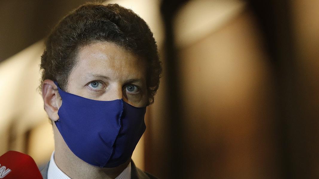 Com uma máscara azul colocada ao contrário, o ministro Ricardo Salles dá entrevista