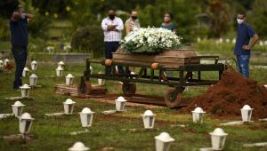 Cinco pessoas, sendo três homens e uma mulher, presenciam o enterro de um ente querido em um cemitério em São Paulo (três delas estão perto uma da outras, enquanto dois homens estão mais distantes)