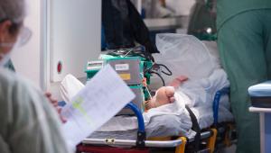 Imagem de uma enfermaria fazendo anotações em frente a um paciente na maca