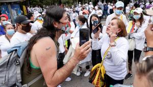"""Um homem discute com uma mulher que participa de uma passeata que rejeita e pede o fim da """"Greve Nacional"""" na COlômbia"""
