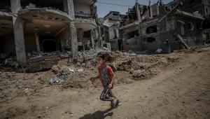 Imagem de criança correndo na Faixa de Gaza. Ao fundo, casas destruídas pela guerra