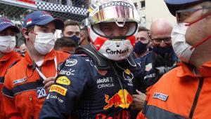 Homem de capacete e macacão azul escuro da Red Bull sorrindo e com pessoas com macacões laranja e máscaras de proteção em volta