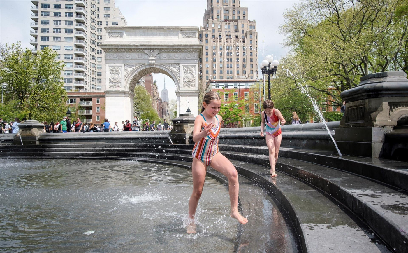 Crianças aproveitam alta das temperaturas para brincar em fonte da Washington Square Park, na cidade de Nova York