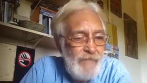 De óculos, barba branca e camiseta azul clara, o cabo Anselmo fala durante gravação de vídeo