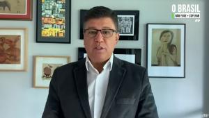 De óculos, cabelo curto, paletó chumbo e camisa branca (sem gravata), Carlos Viana grava depoimento para a Jovem Pan; suas mãos não estão visíveis e alguns quadros aparecem expostos na parede