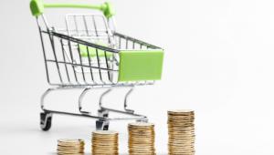 Imagem de um carrinho de compras posicionado atrás de quatro pilhas de moedas, posicionadas lado a lado da mais baixa para a mais alta