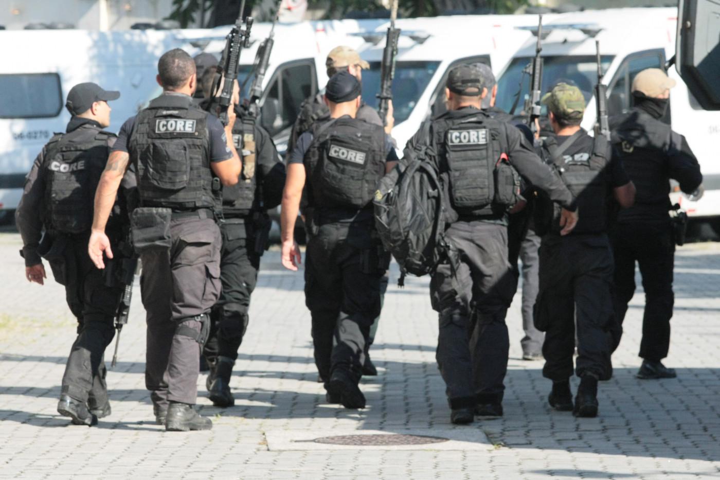 Vários policiais andando uns ao lado dos outros usando fardas e coletes pretos e empunhando armas