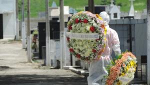 Profissional de cemitério carrega coroas de flores em direção aos túmulos