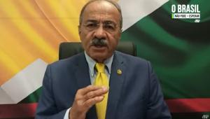 Sentado em uma cadeira, com a bandeira de Roraima atrás, o senador Chico Rodrigues gesticula enquanto grava depoimento à Jovem Pan; o homem de 70 anos usa óculos, mantém um bigode, é calvo (só tem cabelo na parte de trás da cabeça) e veste terno roxo, camisa azul clara e gravata amarela