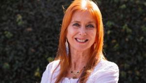 De olhos verdes, cabelos ruivos e uma bata branca, Clélia Angelon sorri para foto
