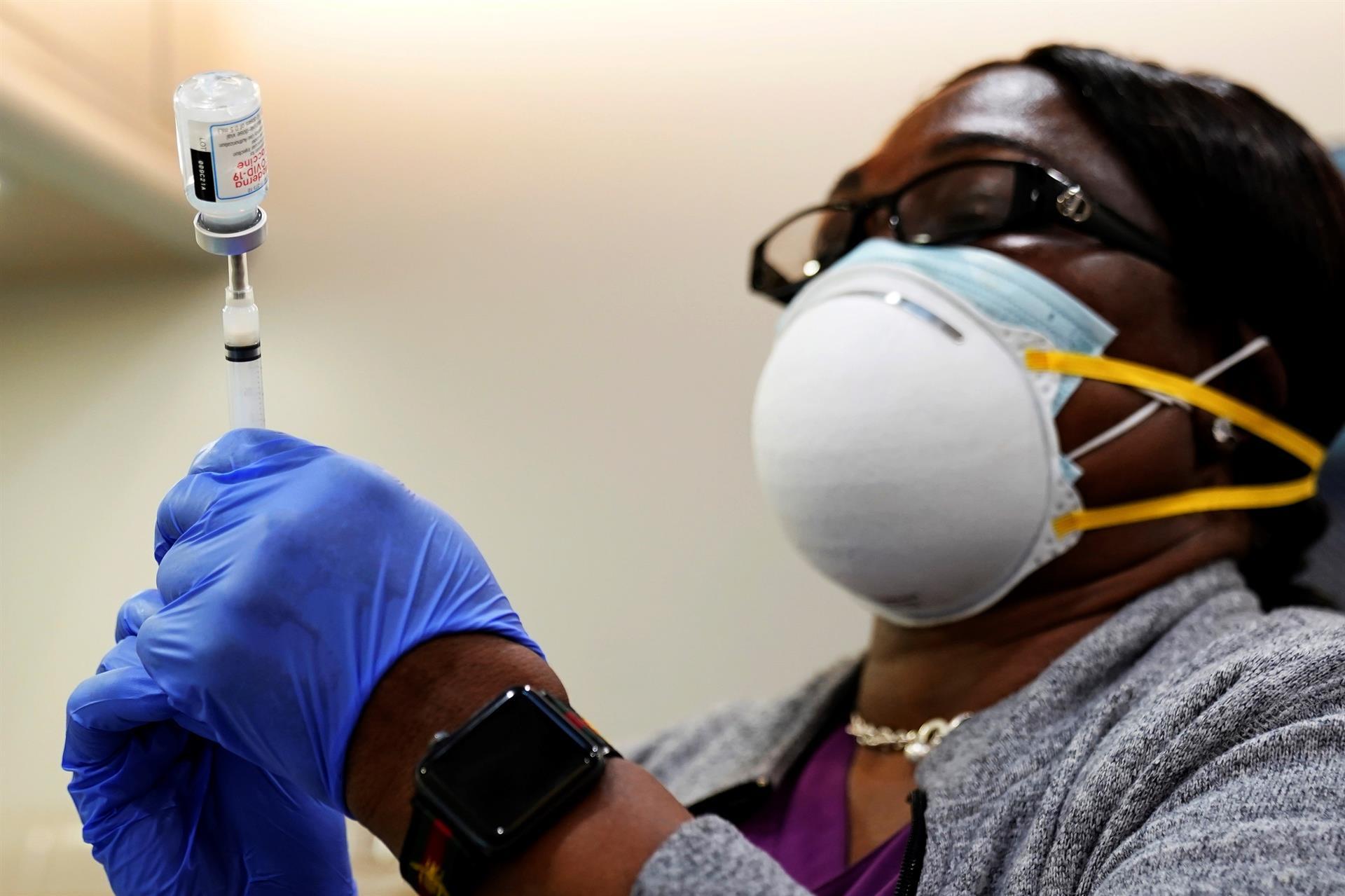 Profissional de saúde coloca insumo dentro de vacina