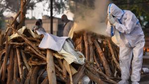 Pessoa usando equipamento de proteção pessoal faz rito de cremação de uma vítima da Covid-19 em Nova Délhi