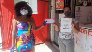 Colaboradora do Bando de Alimentos entregando cartão para compra de alimentos