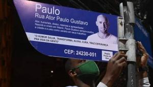 Homem instalando placa de rua em homenagem a Paulo Gustavo