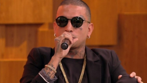MC Guimê usando um óculos de sol e falando no microfone no encontro
