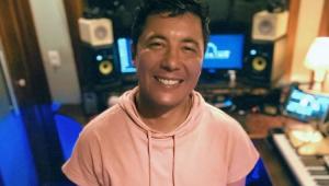 Jhean Marcell sorrindo em um estúdio de música