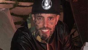 Tico Santa Cruz usando um boné e sorrindo